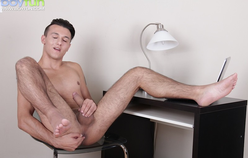 Young twink executive Joseph Sydney strips out of his office clothes and jerks his big uncut cock
